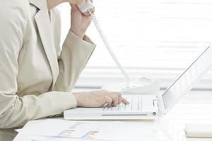 die Geschäftsfrau, die einen Notiz-PC betreibt foto