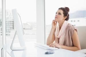 hübsche Geschäftsfrau, die auf Tastatur tippt und denkt