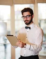 junger Geschäftsmann, der im Büro mit Tablette arbeitet foto