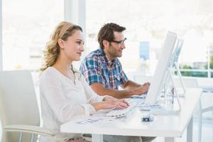 nachdenkliche Bildbearbeiter, die auf ihre Bildschirme schauen foto