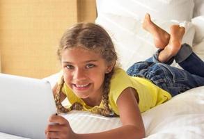 glückliches Mädchen, das auf einem Tablett spielt foto
