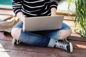 junge Frau, die an ihrem Laptop arbeitet foto