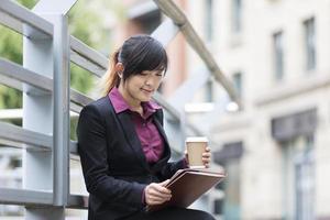 asiatische Geschäftsfrau im digitalen Tablet-PC der modernen Stadt.