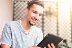 glücklicher Mann benutzt Tablette foto