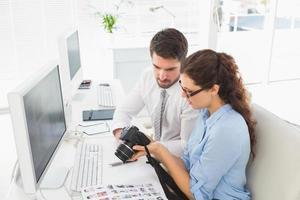 konzentrierte Mitarbeiter halten Digitalkamera