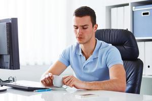 Mann im Büro hält Kaffee foto