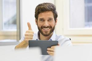ein freudiger Mann, der digitales Tablett hält foto