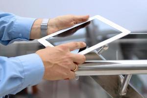Geschäftsmann, der das digitale Tablett hält und benutzt.