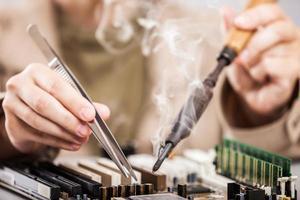 menschliche Hände, die Computerschaltung mit einem Lötkolben reparieren