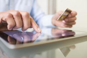 Mann mit Tablet-PC und Kreditkarte drinnen, online einkaufen