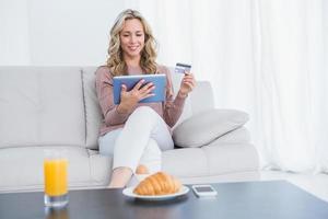 lächelnde Blondine sitzt auf der Couch und kauft online ein