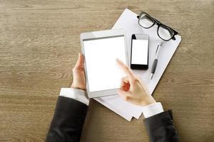 junge Geschäftsfrau, die mit digitalem Tablet-Computer und Smartphone arbeitet