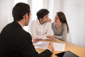 junges Paar, das Immobilienmakler trifft, um Eigentum, Präsentationstafel zu kaufen