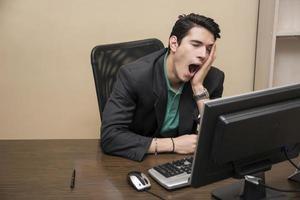 müder gelangweilter junger Geschäftsmann, der im Büro gähnt foto
