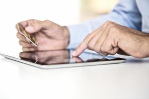 Mann mit Tablet-PC und Kreditkarte drinnen, online einkaufen foto