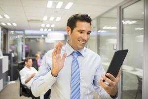 lächelnder Geschäftsmann, der im Internet mit Tablet-PC, Bürohintergrund plaudert foto