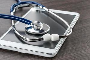 Arztarbeitsplatz mit digitaler Tablette und Stethoskop foto