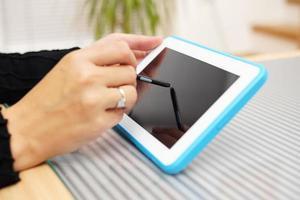Nahaufnahme der Frau, die mit Stift auf Tablette PC arbeitet foto