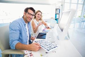 zwei glückliche Bildbearbeiter, die mit Kontaktabzügen arbeiten foto