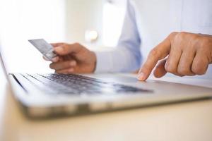 Ein Mann, der mit seiner Kreditkarte online einkauft foto