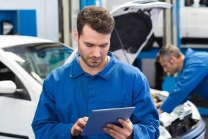lächelnder Mechaniker mit einem Tablet-PC foto