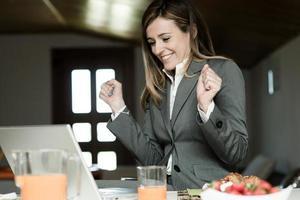 aufgeregte Geschäftsfrau, die während des Frühstücks am PC arbeitet