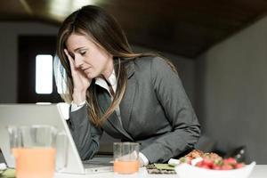 müde / erschöpfte Geschäftsfrau beim Frühstück und Arbeiten foto