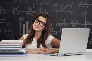Porträt der hübschen jungen Studentin im Klassenzimmer foto