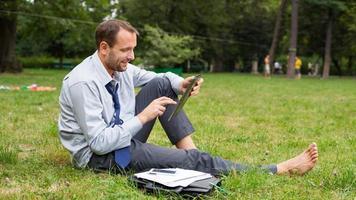 Geschäftsmann am Park mit Tablette, die auf einem Gras sitzt. foto
