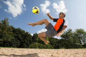 Sportler, der Strandfußball spielt foto