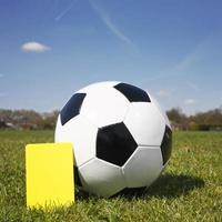 traditioneller Schwarz-Weiß-Fußball mit gelber Karte foto