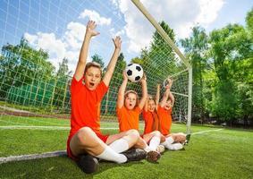 aufgeregte Kinder sitzen mit erhobenem Fußball und erhobenen Armen in einer Reihe