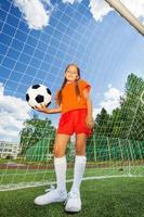 Mädchen hält Fußball, steht vor Holzarbeiten