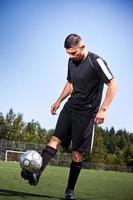 hispanischer Fußball oder Fußballspieler, der einen Ball tritt foto