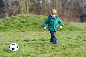 kleiner Junge, der Fußball oder Fußball am kalten Tag spielt