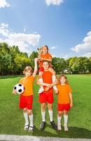 glückliche Kinder mit gewonnenem Pokal stehen in der Pyramide