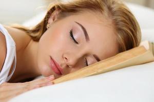 junges schönes blondes Frauenporträt, das im Bett liegt