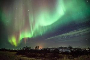 horizontale Zusammensetzung von Aurora Borealis über dem Meer