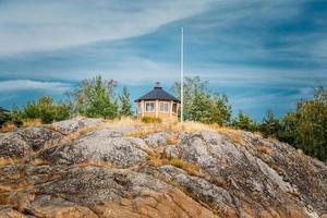 gelbes finnisches Ausguckholzhaus auf Insel im Sommer