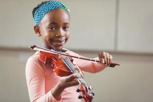 lächelnder Schüler, der Geige in einem Klassenzimmer spielt foto