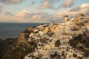 weiße Stadt am Hang des Hügels, Sonnenuntergang, Oia, Santorini, Griechenland foto