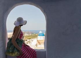 Frau sitzt an einer Wand, Insel Santorini