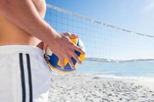 gutaussehender Mann, der Volleyball hält foto