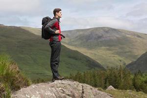Mann, der oben auf dem Hügel steht und die Aussicht bewundert foto