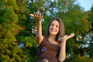 schöne junge Frau, die mit Blasen in einem Park spielt