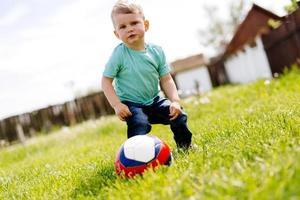 entzückender kleiner Junge, der mit einem Fußball draußen spielt foto