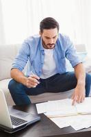 fokussierter Mann, der seine Rechnungen bezahlt foto