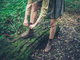 Frau, die ihre Schuhe im Wald bindet foto