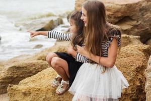 Porträt von zwei niedlichen Schwestern, die am Strand sitzen foto