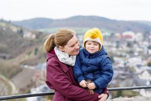 kleines Kind und junge Mutter genießen Aussicht Stadt von oben